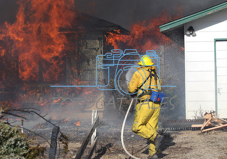 Firefighters battle a 400-acre brush fire in south Reno, Nev., on Friday, Nov. 18, 2011. More than 20 homes have been lost and the fire continues to burn out of control in high winds with gusts up to 60 mph. (AP Photo/Cathleen Allison)