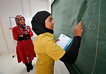 A girl writes on the chalkboard as her teacher looks on during class in the Zaatari Refugee Camp, located near Mafraq, Jordan. Opened in July, 2012, the camp holds upwards of 50,000 refugees from the civil war inside Syria. International Orthodox Christian Charities and other members of the ACT Alliance are active in the camp providing essential items and services.