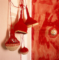 Macrame ornaments hang in the corner of a room against a wall. The opposite wall has a red paint effect.