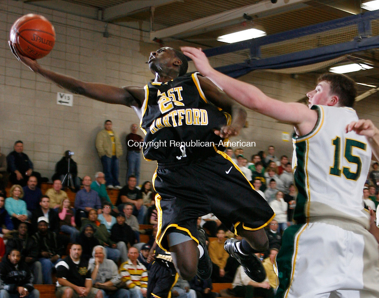 East Hartford's Robert Bentil Jr. beats Holy Cross' Kyle murphy for the layup during Division LL second round action at Holy Cross High School Wednesday night.  The Crusaders were defeated by the Hornets 58-59  Michael Kabelka Republican / American.