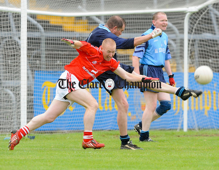Cooraclare's Paddy Harvey gets in his kick despite Crusheen's Gary Seery during their Div 7 Juniuor B Final at Cusack Park. Photograph by John Kelly.