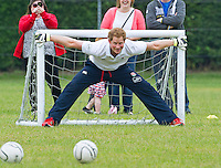 Prince Harry plays football with young children - UK