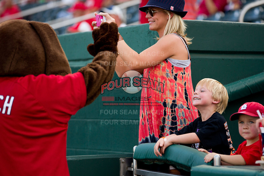 A young fan smiles at Fetch, a Springfield Cardinals mascot, prior to a game between the Arkansas Travelers and the Springfield Cardinals at Hammons Field on July 25, 2012 in Springfield, Missouri. (David Welker/Four Seam Images)