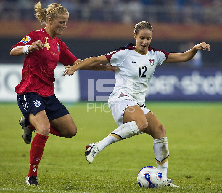 USA midfielder (12) Leslie Osborne tries to get away from England midfielder (4) Katie Chapman. The United States (USA) defeated England (ENG) 3-0 during a quarter-final match of the FIFA Women's World Cup China 2007 at Tianjin Olympics Center Stadium in Tianjin, China, on September 22, 2007.