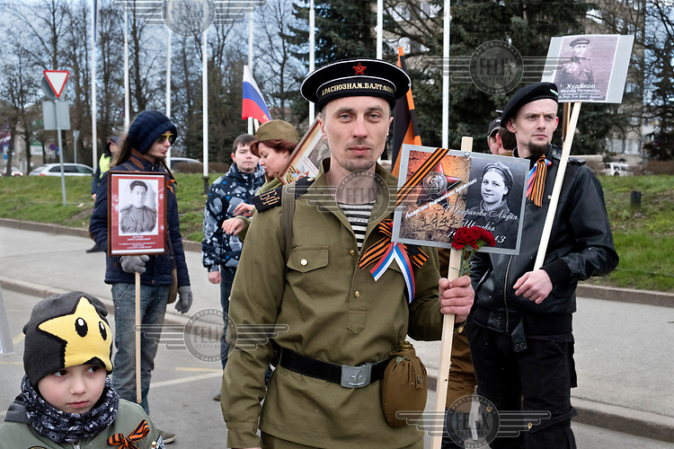 A man dressed in a WWII era Soviet army uniform holds a photograph of Lydya Trufanova, a Red Army soldier killed in 1943. The man, and others behind him, are members of the Association for Memory, an organisation sustaining the Russian view of WWII which is mainly supported by people with Russian ancestry.