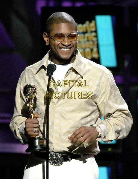 USHER.Receives an award at the 15th Annual World Music Awards held at The Thomas & Mack Center in Las Vegas, Nevada, USA, September 15th 2004..half length on stage sunglasses beige cream shirt white trousers trophy.Ref: DVS.www.capitalpictures.com.sales@capitalpictures.com.©Capital Pictures.