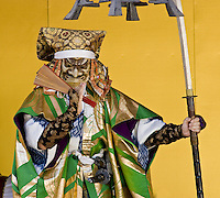 A performer in traditional dress dances with a spear at a stage show in Kyoto, Japan.