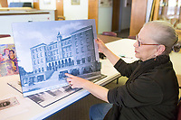 NWA Democrat-Gazette/CHARLIE KAIJO Monte Harris, adult program presenter of the Rogers Historical Museum, points at a picture of old shopping suites that were once attached to the Lane Hotel, which is now Haas Hall on Poplar Street, Friday, March 30, 2018 at the Rogers Historical Museum Education Annex in Rogers. <br /><br />Collectors from the group Finders Keepers share antiques with each other. They will hold meetings on the last Friday of every month from March until September at the Rogers Historical Museum Education Annex until the Rogers Historical Museum completes its expansion. Attendees may share antiques but the group does not provide appraisals for items.