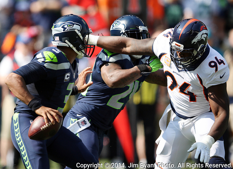 Seattle Seahawks quarterback Russell Wilson (3) scrambles away from Denver Broncos defensive end DeMarcus Ware (94) at CenturyLink Field in Seattle, Washington on September 21, 2014.  Wilson completed 24 of 34 passes for 258 yards, two touchdowns and one interception in the 26-20 overtime win against the Broncos.  ©2014. Jim Bryant Photo. All rights Reserved.