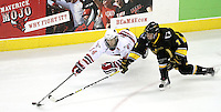 UNO's Joey Martin leaves the ice to knock the puck away from Michigan Tech's Patrick McCadden. UNO defeated Michigan Tech 3-1 Friday night at Qwest Center Omaha. (Photo by Michelle Bishop)
