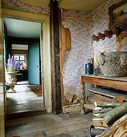 Peeling wallpaper in a storage room filled with firewood and unused furniture reveals the wood-panelled walls beneath