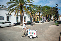 An icecream vendor crosses the street near the Plaza Santo Domingo. Oaxaca City, Oaxaca, Mexico