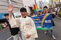 A priest at a gay-friendly church marches in the parade at The Rainbow Pride Event in Shibuya, Tokyo, Japan. Sunday, April 26th 2015. This is the forth annual celebration of LGBT issues in Tokyo and forms part of a wider Rainbow Week. About 5% of the Japanese population identify as homosexual and this event hopes to foster a society where they can live equally and without prejudice.