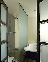 A view through an open door of a modern shower area with an opaque screen, the other side of which is an old fashioned freestanding roll top bath.
