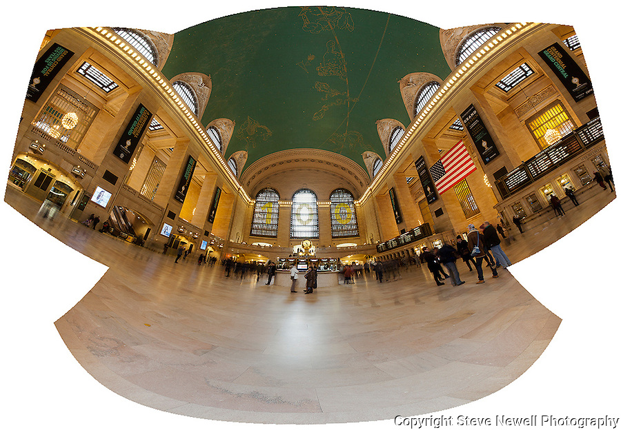 """Grand Central Flight"" Panoramic Grand Central Terminal Manhattan New York.  I was very fortunate to be able to schedule an hour on the main floor of the Terminal during such a special year. It was the 100th Year Anniversary for the building.  I wanted to try and capture the light coming through the three windows like in the famous classic old photograph taken when the building was first constructed. When I applied for my photography permit(only one photographer allowed on the floor at a time) I was informed that the light to the windows is blocked by the tall buildings that were added after the Terminal's construction. They did however add the large numbers in the windows to celebrate the 100th Anniversary. I have several photographs that have the ceiling with the constellations in view and the incredible chandeliers that hang in surrounding rooms just off the main floor.  I put my camera on the floor and used my remote to fire the shutter to compose the ceiling with the arches of the windows in view. I also have a couple of panoramic photographs that have transparent travelers in motion moving through and cover the entire width of the main floor."