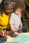 """Preschool 3-4 year olds female teacher with boy writing """"letter"""" to mother to help with separation at start of day vertical"""
