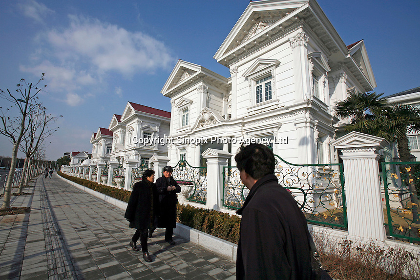 Pedestrians walk past an expensive villa neighborhood in Shanghai, China..