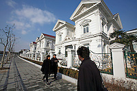 Pedestrians walk past an expensive villa neighborhood in Shanghai, China..