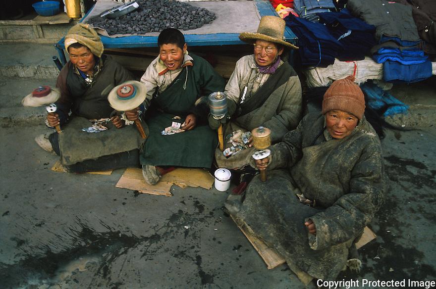 4 damer sveiver b¯nnehjulet og synger, opplevelse, Lhasa, Tibet, Kina
