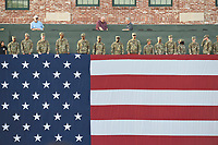 Soldiers unfurl an American flag over the left field wall before the Greenville Drive's home opening game against the Rome Braves on Thursday, April 12, 2018, at Fluor Field at the West End in Greenville, South Carolina. Greenville won, 14-4. (Tom Priddy/Four Seam Images)