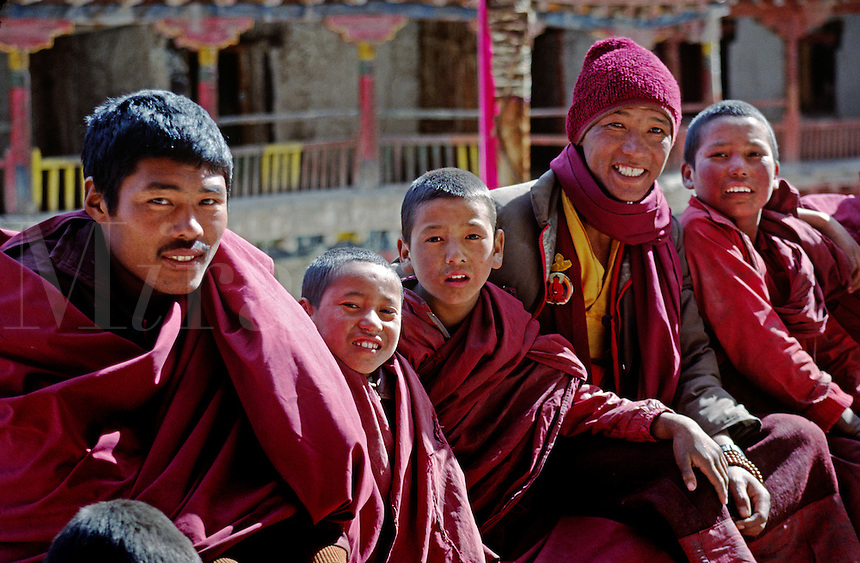 YOUNG MONKS sit in an upper courtyard of  HEMIS GOMPA (monastery) - LADAKH, INDIA.