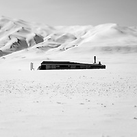 A house submerged in deep snow in Mestersvig. Mestersvig is a military outpost with a runaway in the Scoresby Land region of the Northeast Greenland National Park. Originally built in anticipation of mining in the area it has been run by the Danish defence department since 1988. The place is staffed by two men whose duties include maintenance of buildings and the airfield and support of other activities in the area.