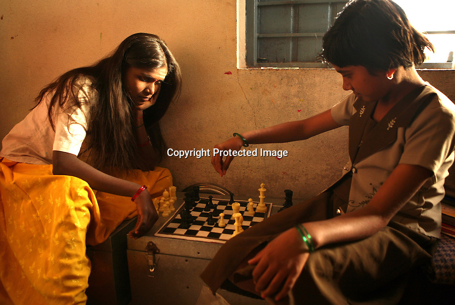 Malashri Kamble, 16 (left) and Saraswati Patil, 11, play chess at their hostel  at Vimochana Sangha's school for the children of Devadasis in Malabad, India.  Kamble's mother was a Devadasi who died at a young age and Kamble was recruited for the school by a social worker when she was 10 years old. The school, which was founded in 1990 by Mr. B.L. Patil, is the first residential school established to break the cycle of the Devadasi system.  Because the belief is that all female children of Devadasis should themselves become Devadasis, the school was created to remove the children from the culture in which this practice took place and instead offer them an education.  All students receive free tuition, books, uniforms, food and medical care. Graduates have gone on to become teachers, nurses, engineers etc. Kamble's grandmother has reservations about Kamble continuing with her studies.  .