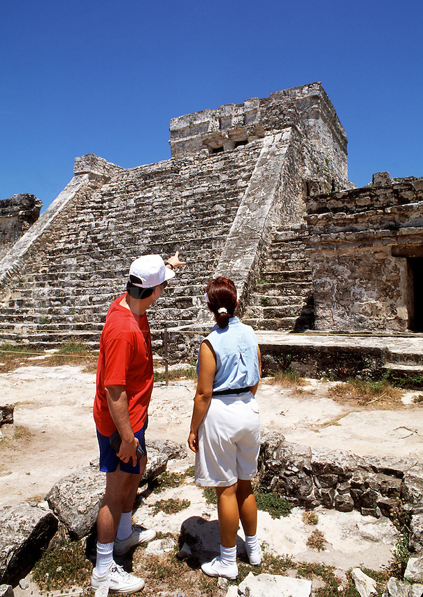 A tourist couple points upwards at the stone steps of the Tulum Mayan ruins. Mexico.