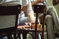 Using a chair as a table at the outside seating terrace in the back yard. Wine bar les Enfants Rouges in Paris. Paris, France.