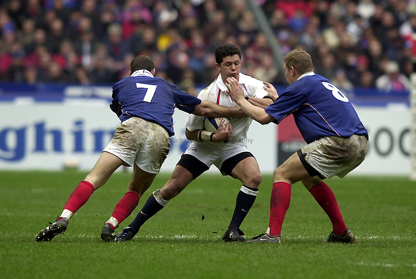 Photo.Richard Lane.France v England at Stade de France. 2-3-2002. Lloyds TSB Six Nations Championship..Henry Paul, on his England debt, is tackled by Olivier Magne (lt) and Imanol Harinordoquy.