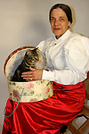 A woman petting a kitten in a hat box
