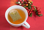 Cup of tea with holiday berries on red background