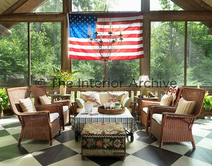 The covered porch has a hand-painted black and white check floor and an American flag hanging from a cross beam