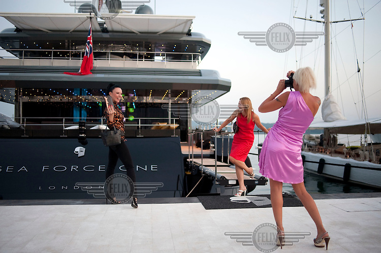 Visitors to the opening ceremony of Porto Montenegro, a  marina and resort on the Adriatic coast, photograph each other by a luxury yacht..