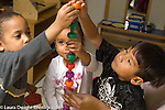 Education preschool 3-4 year olds horizontal group of two boys and a girl working together to build stacking peg tower