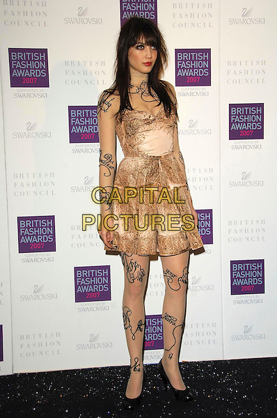 DAISY LOWE.Arriving at the British Fashion Awards 2007 at the Horticulutral Hall London, Engalnd, .27th November  2007..full length writing on skin body art tattoos cream gold beige strapless dress.CAP/CAS.©Bob Cass/Capital Pictures.
