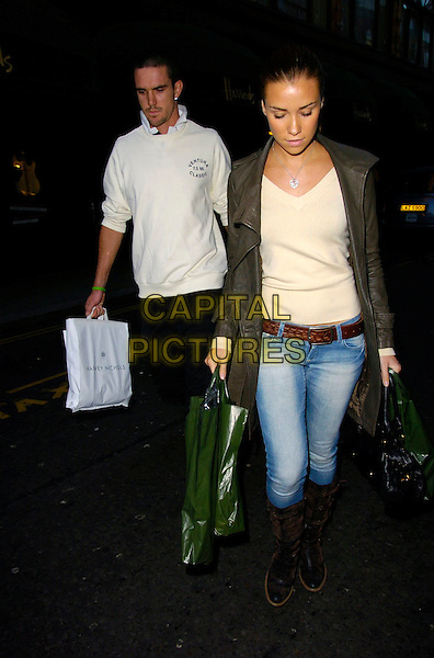 KEVIN PETERSEN & JESSICA TAYLOR.Shopping at Harrods, London, UK..February 1st, 2007.full length tracksuit bottoms grey gray leather jacket jeans denim tucked into black boots bags.CAP/CAN.©Can Nguyen/Capital Pictures