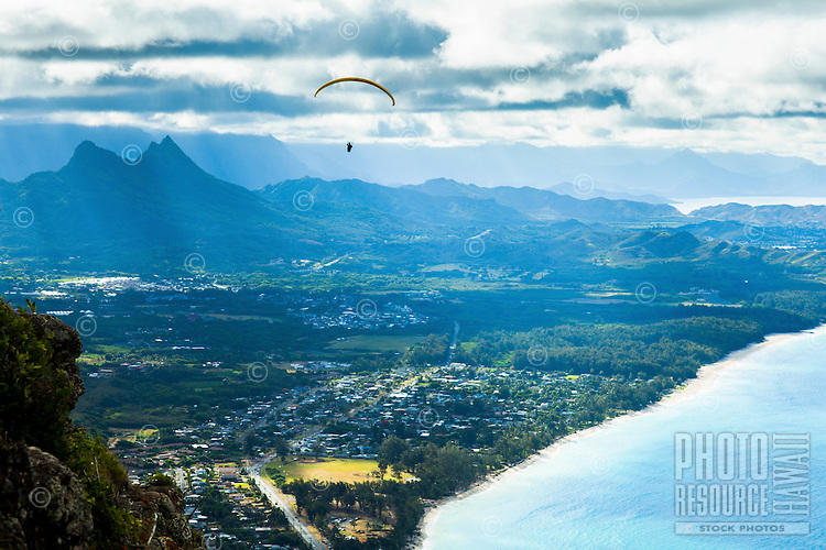 A hang glider drifts towards Mount Olomana on Windward O'ahu, with Waimanalo Beach in the foreground.