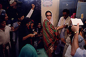 Larkana, Pakistan<br /> November 16, 1988<br /> <br /> Benazir Bhutto arrives at a voting station in Larkana to cast her ballot.<br /> <br /> Benazir Bhutto is the eldest child of former Pakistan President and Prime Minister Zulfikar Ali Bhutto. She found herself placed under house arrest in the wake of her father's imprisonment and subsequent execution in 1979. In 1984 she became the leader in exile of the Pakistan Peoples Party (PPP), her father's party, though she was unable to make her political presence felt in Pakistan until after the death of General Muhammad Zia-ul-Haq. <br /> <br /> On 16 November 1988 Benazir's PPP won the largest bloc of seats in the National Assembly. Bhutto was sworn in as Prime Minister in December, at age 35 she became the first woman to head the government of a Muslim-majority state in modern times. <br /> <br /> She was removed from office 20 months later under orders of then-president Ghulam Ishaq Khan for alleged corruption. Bhutto was re-elected in 1993 but was again removed by President Farooq Leghari in 1996, on similar charges. Bhutto went into self-imposed exile in Dubai in 1998, until she returned to Pakistan on October 2007, after General Musharraf granted her amnesty and all corruption charges withdrawn.