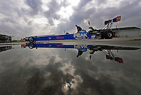 Sept. 1, 2012; Claremont, IN, USA: NHRA top fuel dragster driver T.J. Zizzo reflects in a rain puddle as his car is towed back to the pits during qualifying for the US Nationals at Lucas Oil Raceway. Mandatory Credit: Mark J. Rebilas-