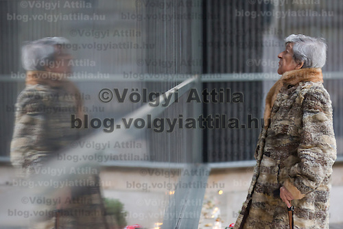 Hungarian Holocaust survivor Erzsebet Brodt, 86, lights a candle in front of a wall bearing the names of victims at Budapest's Holocaust Memorial Centre in Budapest, Hungary on January 27, 2013. ATTILA VOLGYI