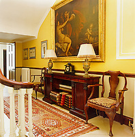 This landing is furnished with a mahogany period sideboard and a pair of matching table lamps and armchairs