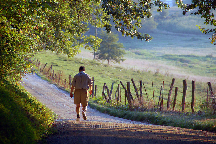 photo by Phil Grout..Alex Graper walks through a land that time forgot as he emerges.from an oak forest  along the gravel portion of Hughes Shop Road.at the north edge of Pleasant Valley.  It's a land of hand-split locust.post fences, verdant pastures and rolling hills running down to.the setting sun.