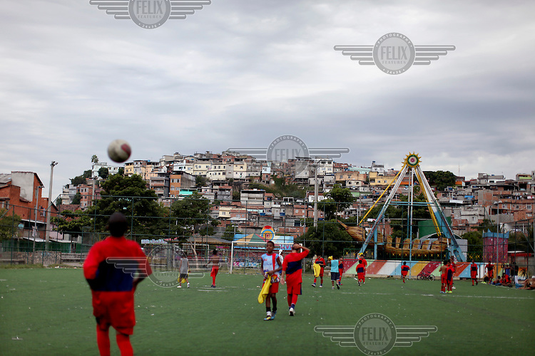Boys play football on a pitch that was once under water. It was part of the Bay of Guarabara, in Complexo da Mare. The favela consists of a complex of 16 communities, in the north zone of Rio de Janeiro. It is the largest complex of favelas, housing 130,000 residents. It is targeted for pacification as the city prepares for the 2014 World Cup and the 2016 Olympics. Four factions run the complex, three drug gangs and the militia. The rival gangs fight for control of the drug trade. Although crime is low in the favelas by rule of law enforced by the gangs, cross-fire shootings and gang violence is often high. Neighborhood associations are an integral part of community development within Mare, making up for a lack of government assistance.