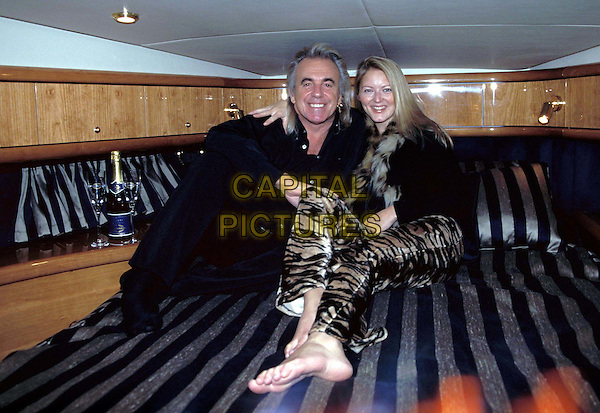 PETER STRINGFELLOW & LUCY CARR.Ref: 9254.sitting, bed, animal print trousers, full length, full-length.www.capitalpictures.com.sales@capitalpictures.com.©Capital Pictures