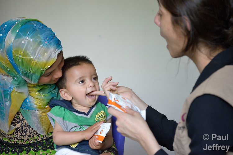 Maha Haidar, a health and nutrition specialist with International Orthodox Christian Charities, a member of the ACT Alliance, feeds Plumpy'Nut to 11-month old Abdul as his mother, Rokaya Al Ali, holds him in the community health center in Kab Elias, a town in Lebanon's Bekaa Valley which has filled with Syrian refugees. Lebanon hosts some 1.5 million refugees from Syria, yet allows no large camps to be established. So refugees have moved into poor neighborhoods or established small informal settlements in border areas. International Orthodox Christian Charities provides support for the community clinic in Kab Elias, which serves many of the refugees. Plumpy'Nut is a specially formulated peanut-based food for treating severe acute malnutrition.