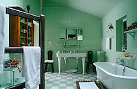 In the bathroom the ceilings and walls are lined in  tongue-and-groove painted a cool green which is picked up in the green and white checkerboard tiled floor
