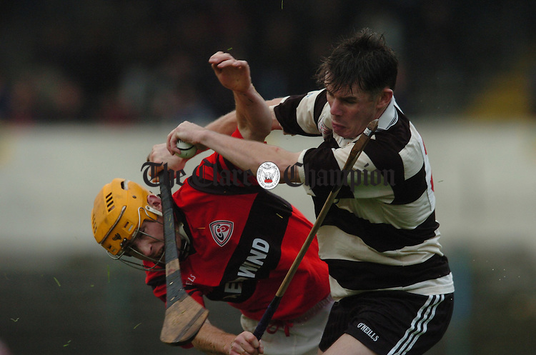 Clarecastle's Martin Sheedy bursts out of defence and meets Whitegate's John Minogue on the way during their game in Cusack Park. Photograph by John Kelly.