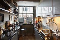 The galley kitchen has a counter made of black Belgian hardstone complimented with silver coloured units