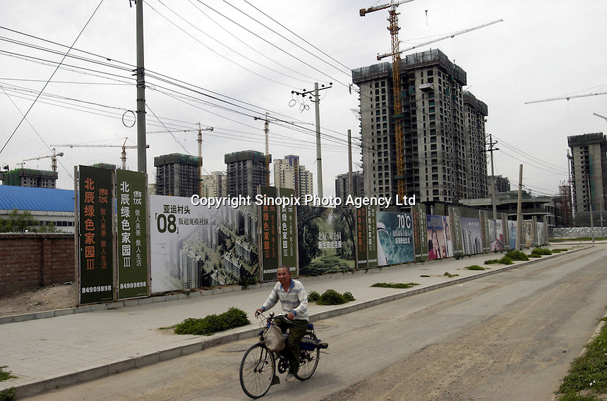An elder man cycles past a construction site at a luxury real estate development near the future Olympic Green which is the main and central district for 2008 Olympic Game in Beijing, China..29-MAY-04